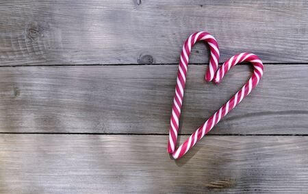 vintage romantic card with candy canes forming a heart on a wooden background