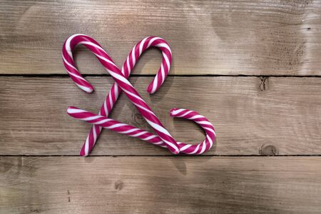 group of candy canes on a rustic wooden planks background