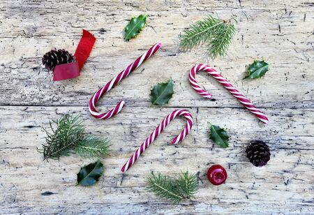 top view on candy canes and christmas decoration on rustic wooden background