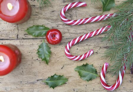 top view on candy canes and christmas decoration with canddles on rustic plank