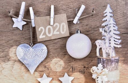 2020 on paper sign and christmas decoration janging to a string on wooden background