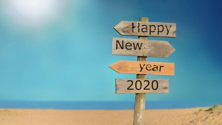wooden signpost happy new year 2020 on the sky and beach background