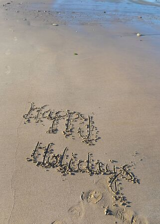 happy holiday hand written on the sand in the beach