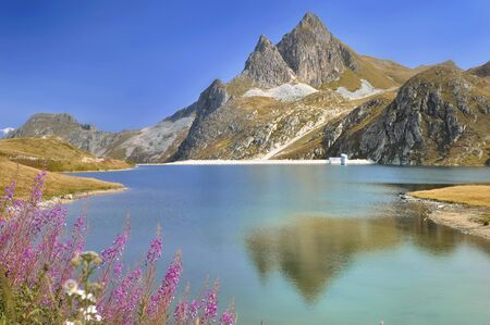 beautiful blue water of a alpine lake surrouded by mountain peaks Фото со стока