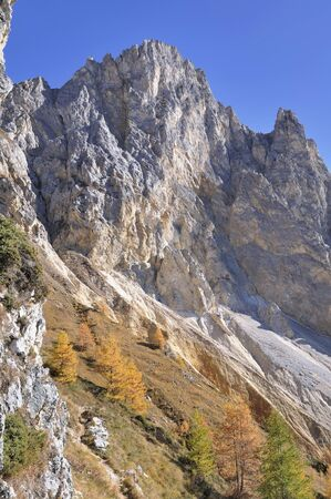 rocky peak mountain with autumnal colors in european Alps  Фото со стока
