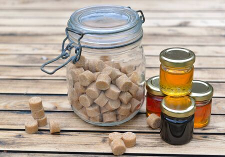 little glass pots of various honey and brown sugar on a wooden table  Фото со стока