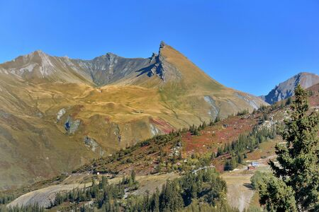 view on alpine mountain covered with yellow and red colors in autumn  under blue sky