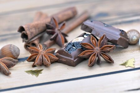 group of spices and chocolate with christmas confetti on a wooden table