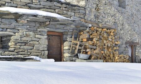 facade of a traditional alpine house stoned with firrewood piled in winter