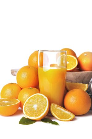 glass on freshness orange juice among heap of fruits on white background