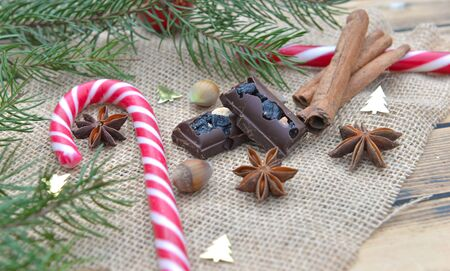 natural christmas decoration with branch of fir spices and chocolate on a textile