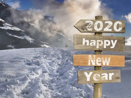 2020 happy new year writting on wooden post sign in front of a scenery sunset in snowy mountain