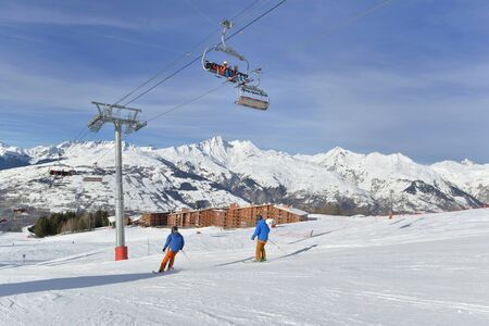 skiers on slopes and chairlifts in alpine resort