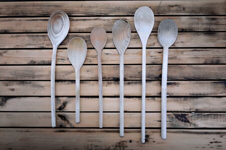 top view on rustic wooden spatula and spoons arranged on a plank
