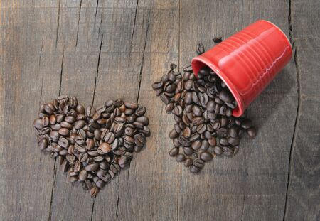 pile of coffee beans forming a heart next to a spilled red cup on rustic wooden background Archivio Fotografico - 138044421