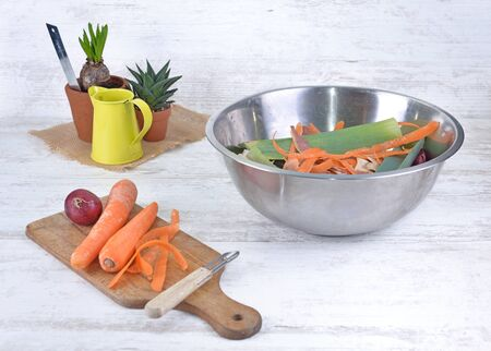 peeling carrots on a cooking plank and bowl full of waste on a table in a kitchen