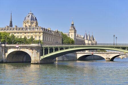 view on ancient building of the conciergerie and bridge of Sully from river the seine