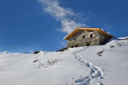 traditional alpine chalet at the top of snowy mountain under blue sky Stock Photo