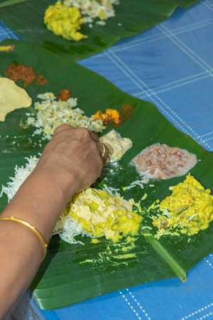 Traditional Kerala food being eaten on a banana leaf during the Onam festival in Kerala India
