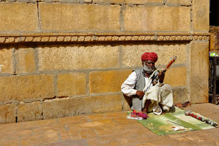 A man wearing turban is siting on ground and playing vilolin at Jaiselmer Rajasthan India on 21 February 2018 Redakční