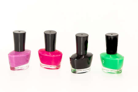 Shallow depth of field image of Four bottles of colored nail polish kept in a pattern with white background