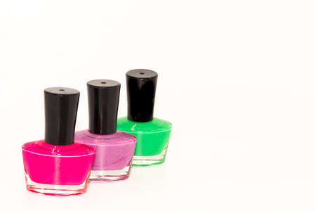 Shallow depth of field image of Three bottles of colored nail polish kept on display with white background Zdjęcie Seryjne
