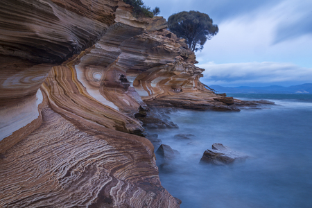 Eroded layers of iron oxide form interesting patterns at the Painted Cliffs on Maria Island National Park in the East coast of Tasmania. The layers are believed to originate from dolerite Jurassic-aged peaks now known as Bishop and Clerk. During erosion,
