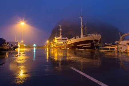 A ship is docked in the harbor of Heimaey in the Westman Islands (Vestmannar) south from Iceland. In the background, volcanic rock formations That shield the harbor from the rough sea disappear into the fog.