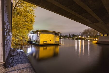 amstel: Night scene with houseboat situated under a bridge in the Amstel river in Amsterdam, Netherlands