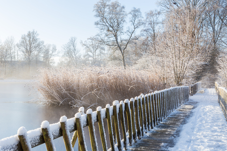 drove: Snow-covered footbridge and drove in a frozen lake melting on a sunny morning in the botanic garden (De Braak, Amstelveen, Netherlands)