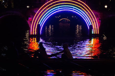 gilbert: Rowers pass by the artwork Bridge of the Rainbow by Gilbert Moity in a canal on the boat route Watercolors at the Amsterdam Light Festival 2016 Stock Photo