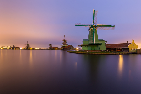 zaandam: Night time landscape of the river Zaan with four windmills lined up at De Zaanse Schans in Zaandam, the Netherlands. Lights from street lamps and houses are reflected on the water surface. Sky is brightly colored in a gradient by city lights combined wi