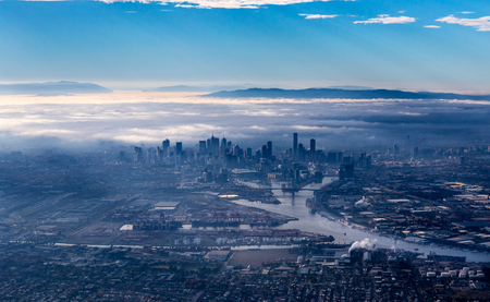 Melbourne skyline with skyscrapers emerging from the morning fog. Early morning aerial view overlooking Yarra river, harbor area and city center. Yarra Ranges National Park is covered by low clouds in the background