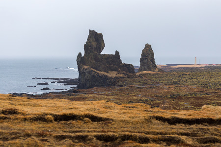 The cliffs at Londrangar, a pair of basalt pinnacles rising from the coastline of the Snaefellsnes peninsula in Iceland. The rock formations remain from volcanic plugs after the softer outer layers of a crater eroded away by elements at the seashore. Stock Photo