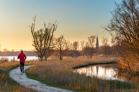 Jogger running on lakeside footpath for outdoor exercise in nature park. Meadows, trees and church in background are lit by early morning sun at sunrise.