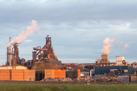 Stará ocelová továrna s kouřovými komíny a emise komínů