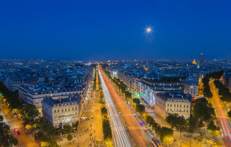 The moon rises above the Champs-Elysees in Paris at nightfall