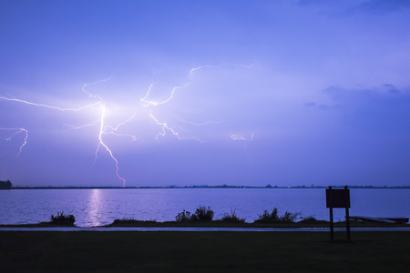 wheater: Lightning strikes above a lake at night coloring the sky blue Stock Photo