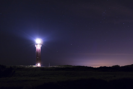 navigational light: A old lighthouse in dunes during a dark night. It functions as a navigational beacon for ships on sea.
