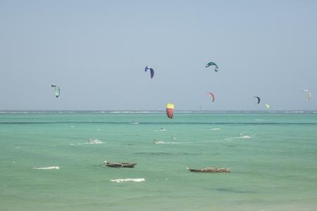 kiting: Kitesurfers kiting near wooden fish boats in the Indian ocean at Tanzania, Zanzibar