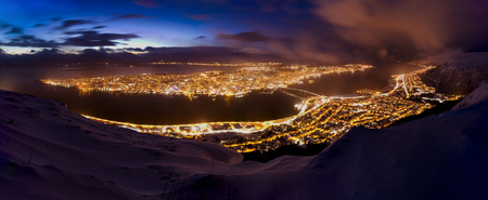 eliminate: Beautiful and colorful panorama view of the city of Tromso, Troms Norway, during dusk. A winter snowstorm is incoming in the valley of Tromso, eliminate the clear sky sunset.