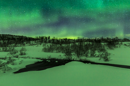 Northern lights Aurora Borealis in the night. A little water stream on the foreground with a arctic, snowy winter landscape. The sky is clear, a lot of stars are visible Stock Photo