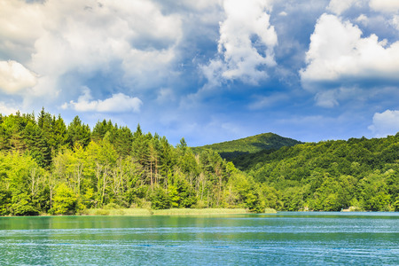 Landscape with mountains on a Summer sunny day with green trees and blue sky and water. Plitvice lakes, Croatia