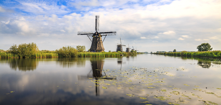 Traditional Dutch Windmills Kinderdijk,  during sunset late summer panorama. Reflection visible on the water surface.