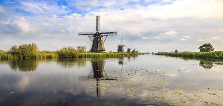 Traditionele Nederlandse windmolens Kinderdijk, tijdens zonsondergang laat zomer panorama. Reflectie zichtbaar op het wateroppervlak.