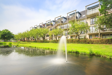 Attractive, decorative water fountain in a pond next to residential houses and apartments on a sunny Summer day located in Zoetermeer, the Netherlands, het Dorp district. Stock Photo