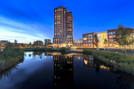 View over water to typically residential apartments towers de Elementen at night near the heemkanaal at the suburban Oosterheem, Zoetermeer, the Netherlands during dusk Stock Photo