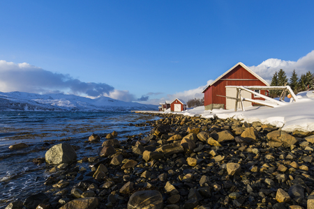 Typical norwegian warm and cozy house located at the lakeside at a fjord in Troms county, Norway. The sun is set low above the horizon and the sky is clear blue. The landscape is covered with snow.