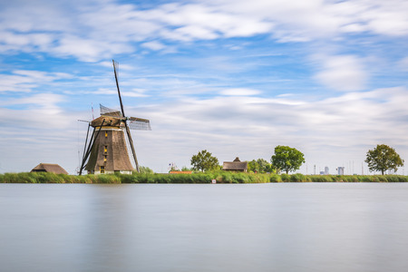Landscape with clouded sky and a old Dutch traditional windmill located at Rottemeren lake near Rotterdam.