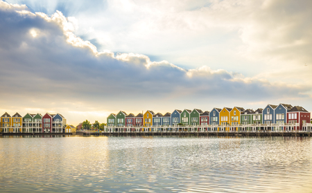 Dutch, modern, colorful vinex architecture style houses at waterside during dramatic and clouded sunset. Houten, Utrecht. HDR Фото со стока